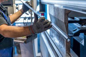 A worker bending a sheet of steel